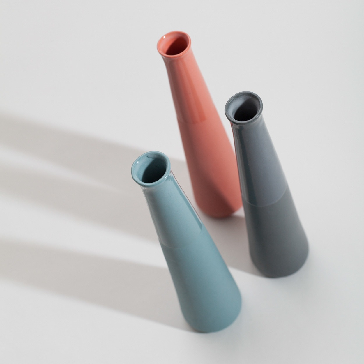 Three vases in red, blue and grey porcelain